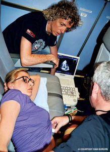 Massimo Pieri observes while Danilo Cialoni uses ultrasound to look for bubbles in a research subject's heart during flight. (Photo from Alert Diver Online)